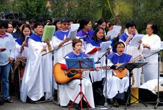 Hong Kong: Choir at Mass in Chater Park. A Filippina women's choir performing hymns with two accompanying guitar players during Mass service in Chater Park at Stock Images