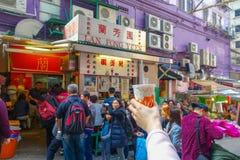 HONG KONG, CINA - 26 GENNAIO 2017: Folla dell'alimento d'acquisto della gente nel supporto della via nella città di Hong Kong Fotografia Stock