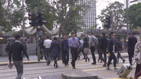 Hong Kong city, China - May, 2019: pedestrian crossing crosswalk on city road. Crowd business people walking on. Crossroads on city building background. Urban stock video