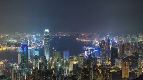 Hong Kong city skyline timelapse at night with Victoria Harbor and skyscrapers illuminated by lights over water viewed stock video footage