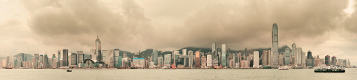 Hong Kong city skyline. Urban architecture in Hong Kong Victoria Harbor with city skyline and cloud in the day with yellow tone royalty free stock photos