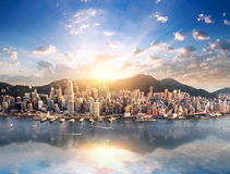 Hong Kong city skyline view from harbor with skyscrapers and sun. Hong Kong city skyline view from harbor with skyscrapers buildings reflect in water at sunset Royalty Free Stock Image