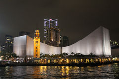 Hong Kong Cultural Centre at Night. Hong Kong Cultural Centre lit up at night with the Clock Tower in the foreground Stock Image