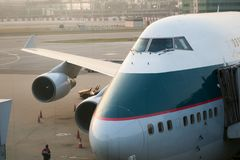 Cathay Pacific Boeing 747-400 Jumbo Jet parks at the gate in front of terminal building royalty free stock image