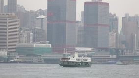 HONG KONG - DEC 23 2016 : Star Ferry is sailing through Victoria Harbour, with the skyline of Hong Kong as backdrop. 4K Video stock video