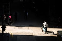 Delivery man pushes a cart across a small junction in the back alley of Hong Kong royalty free stock images