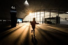 Young girl running excitedly in airport terminal building stock images