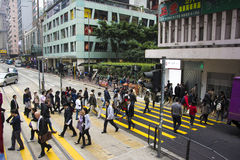 HONG KONG - DECEMBER 12, 2013: Crowd of people crossing the street in front of a tram station. Royalty Free Stock Image