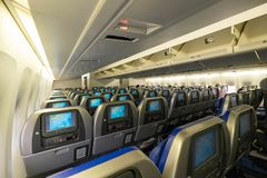 Economy class cabin of Cathay Pacific Boeing 747 with old style in flight entertainment. HONG KONG - DECEMBER 2014: Economy class cabin of Cathay Pacific Boeing royalty free stock images