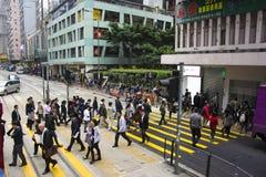 HONG KONG - 12. DEZEMBER 2013: Menge von den Leuten, welche die Straße vor einer Tramstation kreuzen Lizenzfreies Stockbild