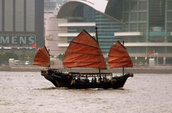 Hong Kong: Dik Luk Chinese Junk. The famous Dik Luk Chinese Junk tourist boat glides past the Hong Kong Convention Center sailing along the waters of Victoria Stock Photos