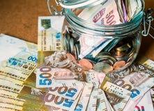 Banknote and coins in glass jar. Hong Kong dollar banknote on the floor and coins in glass jar Royalty Free Stock Photo