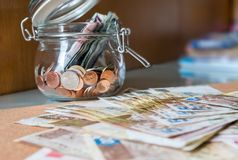 Banknote and coins in glass jar. Hong Kong dollar banknote on the floor and Thai coins in glass jar : Focus on glass jar Royalty Free Stock Images