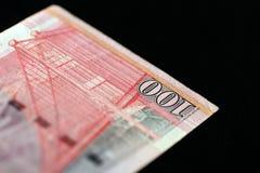 100 Hong Kong dollar på en mörk bakgrund Arkivbild
