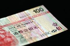 100 Hong Kong dollar på en mörk bakgrund Fotografering för Bildbyråer