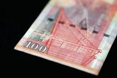 100 Hong Kong dollar på en mörk bakgrund Arkivfoto