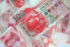Hong Kong dollars. Close up of 100 Hong Kong dollar note with bckground of chinese yuan Royalty Free Stock Photography