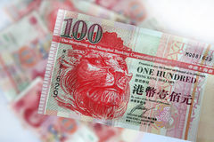 Hong Kong dollars. Close up of 100 Hong Kong dollar note with bckground of chinese yuan