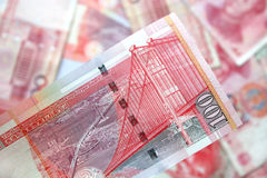 Hong Kong dollars. Close up of 100 Hong Kong dollar note with bckground of chinese yuan Stock Images
