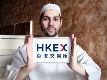 Hong Kong Exchanges and Clearing, HKEX logo. Logo of Hong Kong Exchanges and Clearing, HKEX on samsung tablet holded by arab muslim man. It operates a stock Stock Photo