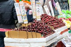 HONG KONG- FEBRUARY 19, 2018-Kawloon - Fruits vendors selling fr. Esh cherry and verity of fruits on street market stalls of Hong Kong,  the seasonal fruits are Stock Image