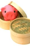 Hong Kong Financial Culture. Two bamboo steaming baskets for dim sum with a piggy bank in one of the baskets - a metaphor for Hong Kong's financial and business Royalty Free Stock Image