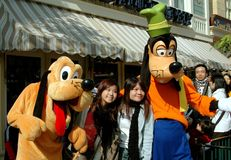 Hong Kong: Goofy and Pluto at Disneyland. Two lovely Asian women pose for photos with famed Goofy and Pluto Disney characters at the Hong Kong Disneyland theme Royalty Free Stock Image