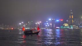Hong Kong Harbor con la nave rossa del ciarpame alla notte stock footage