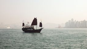 Hong Kong Harbor Wooden Ship sailing with building skyline stock photography