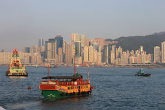 Hong kong harbour boats and skyline. Yellow and red Chinese boats in the Hong Kong Victoria Harbour with the background of Hong Kong Island Stock Images