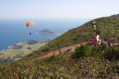 Hong Kong: hikers watch paraglider take off, ocean in background Stock Image
