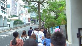 People are traveling in up hill in Hong Kong to The Peak Tram terminal stock footage