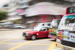 Hong Kong, Hong Kong SAR - 13 de noviembre de 2014: Indique el taxi y los autobuses borrosos durante hora punta en Hong Kong Foto de archivo