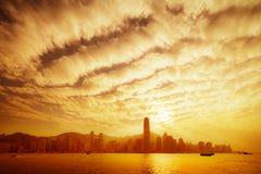 Hong Kong horisont i guld- skymning med dramatiska moln Arkivfoton