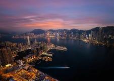 Hong Kong horisont och flyg- sikt för Victoria Harbor afton Royaltyfri Foto