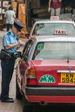 Traffic warden writes a car up for infraction on Hong Kong Island China stock images