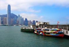 Hong Kong Island-cityscape van Kowloon met veerboten bij pijler royalty-vrije stock afbeelding
