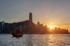 Hong Kong Island skyline at sunset. Sailboat in Victoria harbor stock images