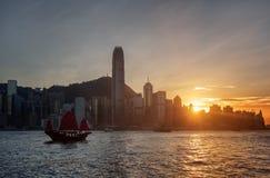 The Hong Kong Island skyline at sunset. Sailing ship in bay Stock Image