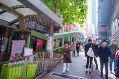 Hong Kong - Januari 13, 2018: Folket flyttar sig upp på rulltrappan på Fotografering för Bildbyråer