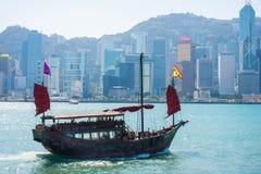 Hong Kong - January 10, 2018 :Chinese wooden sailing ship with r. Ed sails in Victoria harbor at Hong Kong Island, landmark Stock Photography