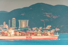 Cargo transportation company vessel loaded with containers ships goods across Lamma Channel in Hong Kong stock image