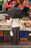 Man holding an umbrella at a stall at Graham Street wet market,. HONG KONG - JULY 26, 2013 - Man holding an umbrella at a stall at Graham Street wet market, Hong Stock Images