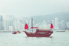 HONG KONG, JUNE 05, 2018 : Traditional Chinese wooden sailing sh. Ip with red sails in Victoria harbor. Skyscrapers in downtown of Hong Kong are visible from Royalty Free Stock Images
