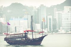 HONG KONG, JUNE 05, 2018 : Traditional Chinese wooden sailing sh. Ip with red sails in Victoria harbor. Skyscrapers in downtown of Hong Kong are visible from Royalty Free Stock Photo