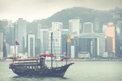 HONG KONG, JUNE 05, 2018 : Traditional Chinese wooden sailing sh. Ip with red sails in Victoria harbor. Skyscrapers in downtown of Hong Kong are visible from Royalty Free Stock Image