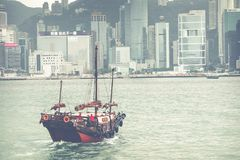 HONG KONG, JUNE 05, 2018 : Traditional Chinese wooden sailing sh. Ip with red sails in Victoria harbor. Skyscrapers in downtown of Hong Kong are visible from Stock Photos