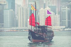 HONG KONG, JUNE 05, 2018 : Traditional Chinese wooden sailing sh. Ip with red sails in Victoria harbor. Skyscrapers in downtown of Hong Kong are visible from Stock Images
