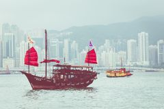 HONG KONG, JUNE 05, 2018 : Traditional Chinese wooden sailing sh. Ip with red sails in Victoria harbor. Skyscrapers in downtown of Hong Kong are visible from Royalty Free Stock Photography