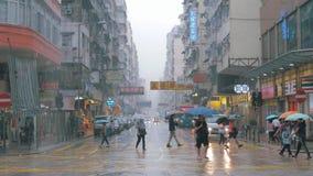 HONG KONG - JUNI 26, 2018: Mensen met paraplu dichtbij de post van Veinzerijshui Po Regen in Hong Kong stock videobeelden